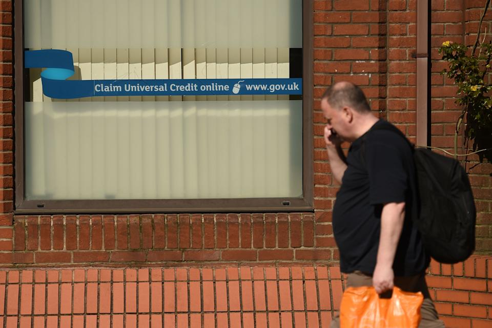 A man walks past a sign with the email address of 'universal credit' outside the offices of 'jobcentreplus' in Oldham, Lancashire on March 26, 2020, during a country-wide lockdown to slow the spread of the novel coronavirus COVID-19. (Photo by Oli SCARFF / AFP) (Photo by OLI SCARFF/AFP via Getty Images)