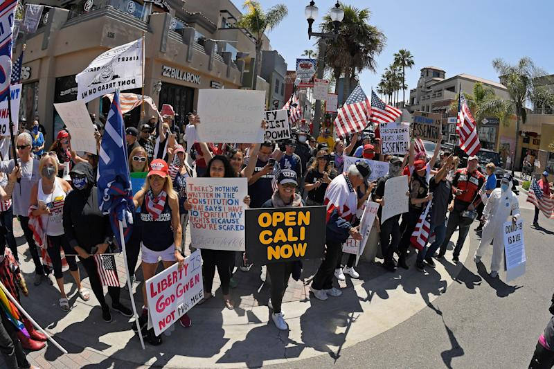 Protesters demonstrate against stay-at-home orders that were put in place due to the COVID-19 outbreak, Friday, April 17, 2020, in Huntington Beach, Calif.
