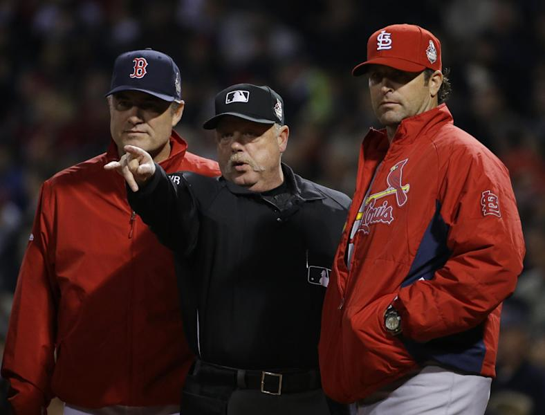 Home plate umpire Adam Wainwright goes over the ground rules with Boston Red Sox manager John Farrell, left, and St. Louis Cardinals manager Mike Matheny before Game 6 of baseball's World Series Wednesday, Oct. 30, 2013, in Boston. (AP Photo/Matt Slocum)