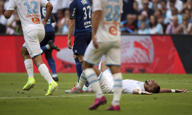 Marseille's Dimitri Payet, right, lays on the pitch after missing a chance during the French League One soccer match between Marseille and Reims at the Velodrome Stadium in Marseille, France, Saturday, Aug. 10, 2019. (AP Photo/Daniel Cole)