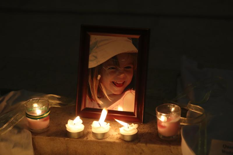 Candles light a photograph of Madeleine McCann inside the church of Praia da Luz, near Lagos, on May 3, 2017, during a mass ceremony marking the 10th anniversairy of her disappearance. Madeleine McCann (Maddie) disappeared in Praia da Luz on May 3, 2007. Portuguese police closed the case in 2008 before reopening it five years later. / AFP PHOTO / POOL / STRINGER (Photo credit should read STRINGER/AFP via Getty Images)
