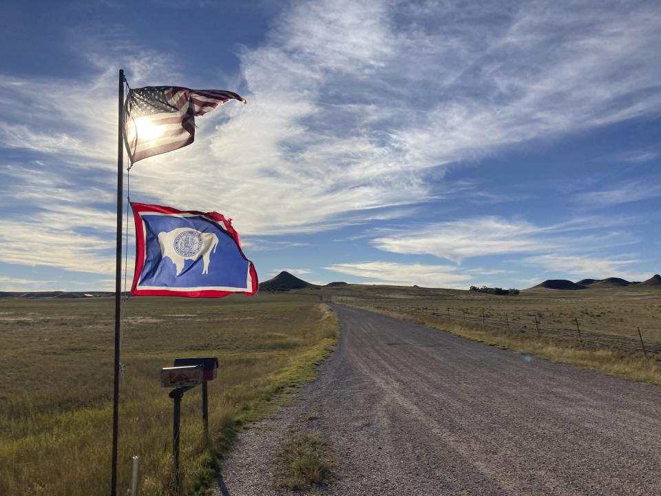 The U.S. and Wyoming flags flutter in the wind next to a rural road south of Gillette, Wyo., on Wednesday, Sept. 22, 2021. Wyoming has the lowest COVID-19 vaccination rate in the U.S. and the Gillette area has one of the lowest rates in Wyoming. (AP Photo/Mead Gruver)