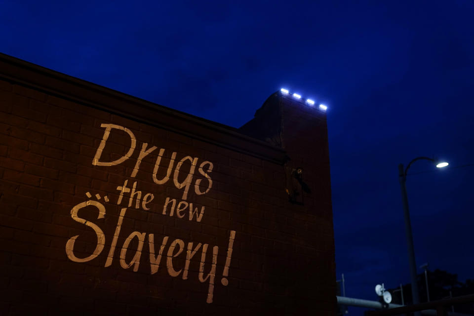 """A sign painted on the side of a corner store reads, """"Drugs... the new Slavery!"""" in St. Louis on Friday, May 21, 2021. As the COVID-19 pandemic intensified America's opioid addiction crisis in nearly every corner of the country, many Black neighborhoods like this one suffered most acutely. (AP Photo/Brynn Anderson)"""