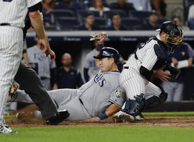 Tampa Bay Rays' Ji-Man Choi, center, slides past New York Yankees catcher Austin Romine to score on a single by Brandon Lowe during the fifth inning of a baseball game Wednesday, Aug. 15, 2018, in New York. (AP Photo/Frank Franklin II)