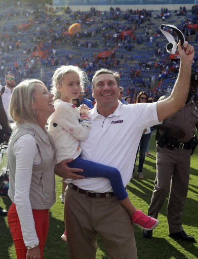 Florida head coach Dan Mullen, right, celebrates with his wife, Megan, left, and daughter Breelyn in front of fans after defeating Vanderbilt in an NCAA college football game, Saturday, Nov. 9, 2019, in Gainesville, Fla. (AP Photo/John Raoux)