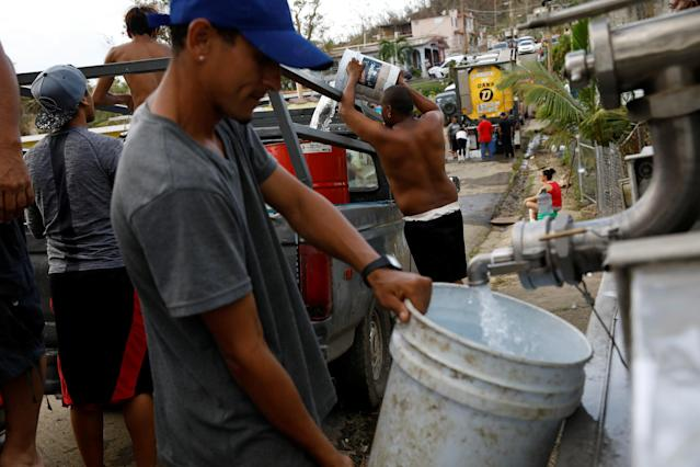 <p>People fill containers with water on the street after the area was hit by Hurricane Maria in Toa Baja, Puerto Rico September 24, 2017. (Photo: Carlos Garcia Rawlins/Reuters) </p>