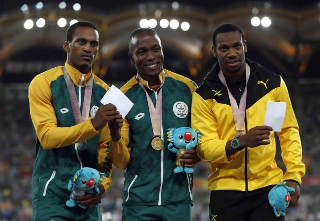 Athletics - Gold Coast 2018 Commonwealth Games - Men's 100m medal Ceremony - Carrara Stadium - Gold Coast, Australia - April 10, 2018. Gold medalist Akani Simbine of South Africa, silver medalist Henricho Bruintjies of South Africa and bronze medalist Yohan Blake of Jamaica pose with medals. REUTERS/Paul Childs