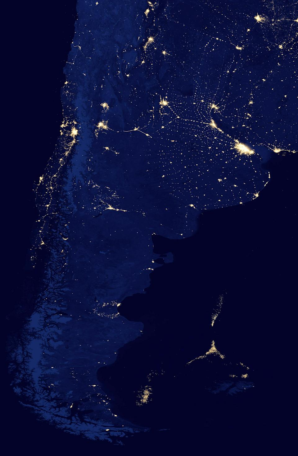 In this NASA Earth Observatory image made available by NASA on March 22, 2013, the southern tip of South America is seen at night in April of 2012. Off the coast, the lights of a huge fleet of shrimp boats can be seen, right along the maritime border between Argentina, the Falkland Islands and international waters. Scientists say this unmanaged fleet is threatening the South Atlantic marine ecosystem by depleting the squid, which are key to a food chain that provides sustenance for penguins, seals, birds and whales. (AP Photo/NASA's Suomi Polar-orbiting Partnership)
