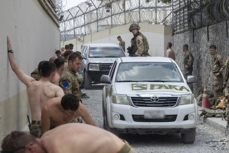 In this handout photo provided by the Ministry of Defence, members of the UK Armed Forces taking part in the evacuation of entitled personnel from Kabul airport in Afghanistan, Friday, Aug. 20, 2021. (LPhot Ben Shread/Ministry of Defence via AP)