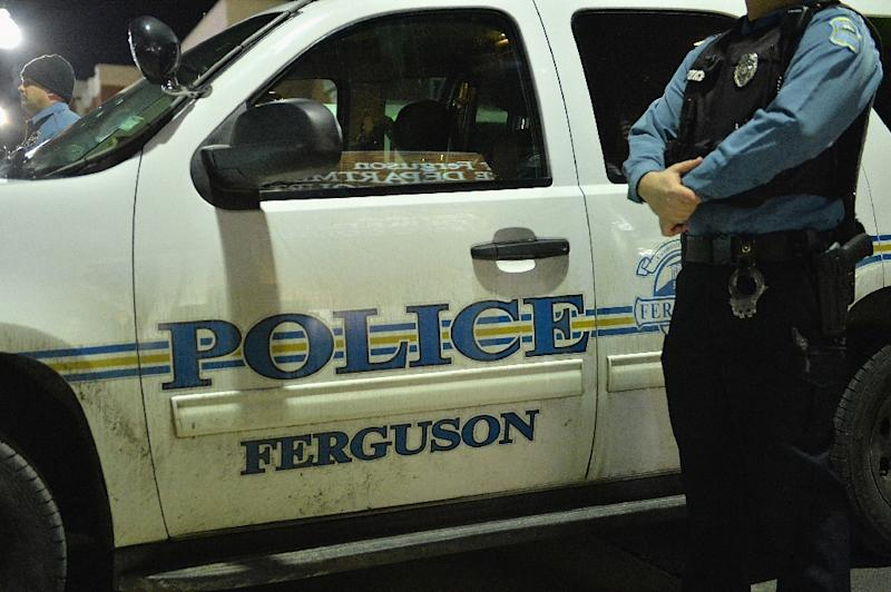 A Ferguson police officer stands on watch as protestors demonstrate outside the Ferguson Police Department in Ferguson, Missouri on March 4, 2015