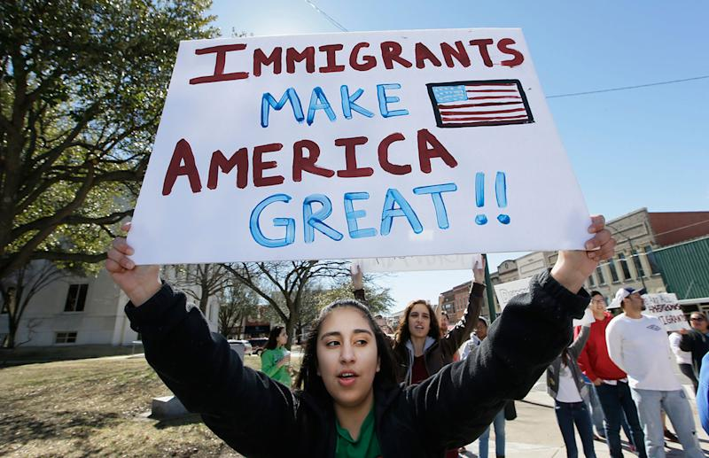 <p>High school student Kathia Suarez holds up a sign as she protests with others outside the Grayson County courthouse in downtown Sherman, Texas, Feb. 16, 2017. (Photo: LM Otero/AP) </p>