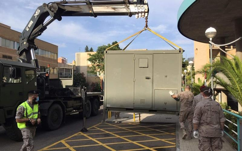 soldiers install modules in the car park of the Hospital Clinico Universitario in Zaragoza, Spain. Spain's army is setting up a field hospital in Zaragoza as the northern city struggles to stop a new spike in cases of the coronavirus. - MDE via AP