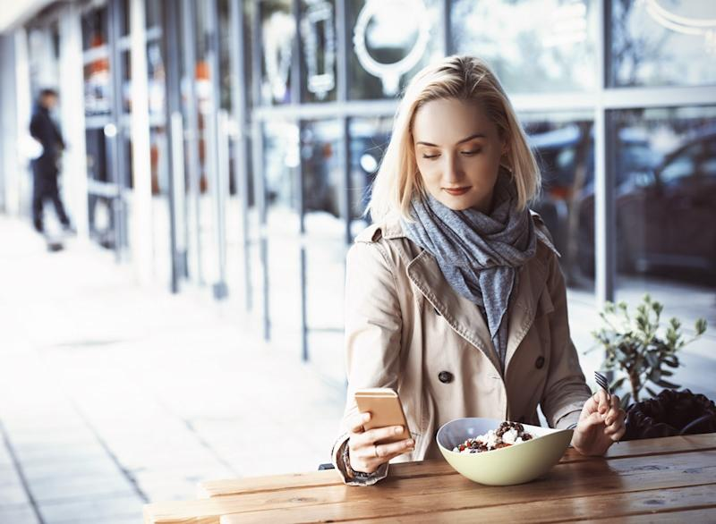 woman on phone while eating