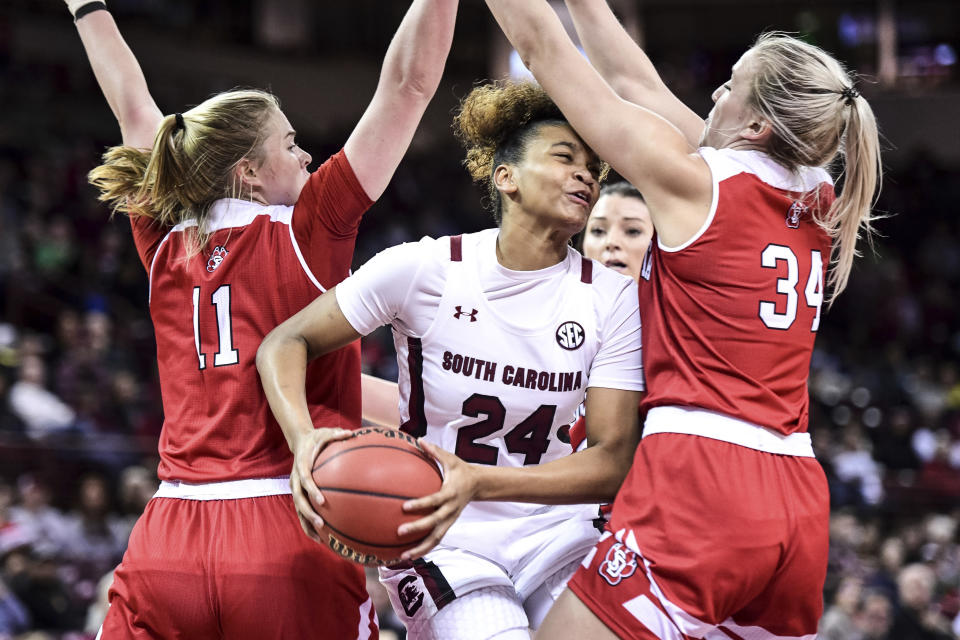 South Carolina guard LeLe Grissett (24) battles in the paint against South Dakota center Hannah Sjerven (34) and Monica Arens (11) during the first half of an NCAA college basketball game Sunday, Dec. 22, 2019, in Columbia, S.C. (AP Photo/Sean Rayford)