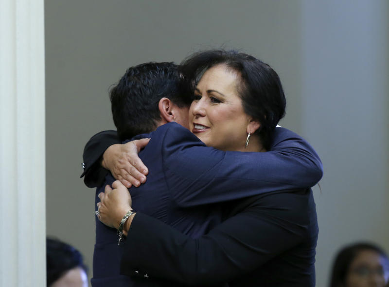 Assemblywoman Lorena Gonzalez, D-San Diego, receives congratulations from Assembly Speaker Anthony Rendon, of Lakewood after her to give new wage and benefit protections at the so-called gig economy companies like Uber and Lyft was approved by the Assembly in Sacramento, Calif., Wednesday, Sept. 11, 2019. The bill now goes to the governor, who has said he supports it. (AP Photo/Rich Pedroncelli)