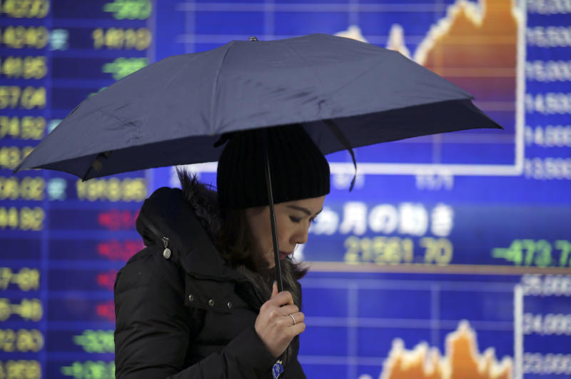 A woman walks by an electronic stock board of a securities firm in Tokyo, Tuesday, Feb. 4, 2014. Weakness in U.S. and Chinese manufacturing sent Asian stock markets sharply lower Tuesday. (AP Photo/Koji Sasahara)