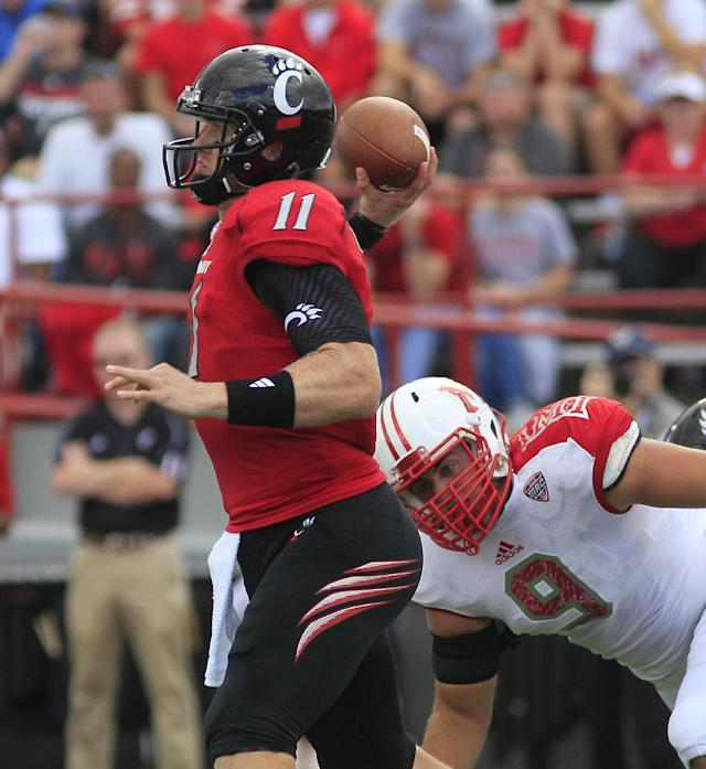 Cincinnati quarterback Brendon Kay (11) throws a pass as he is pressured by Miami (Ohio) defensive lineman Wes Williams (9) in the first half of an NCAA college football game, Saturday, Sept. 21, 2013, in Oxford, Ohio. (AP Photo/Tony Tribble)
