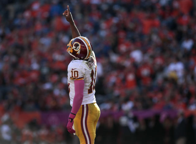 Washington Redskins quarterback Robert Griffin III (10) points skyward after throwing a touchdown pass against the Denver Broncos in the second quarter of an NFL football game, Sunday, Oct. 27, 2013, in Denver. (AP Photo/Joe Mahoney)