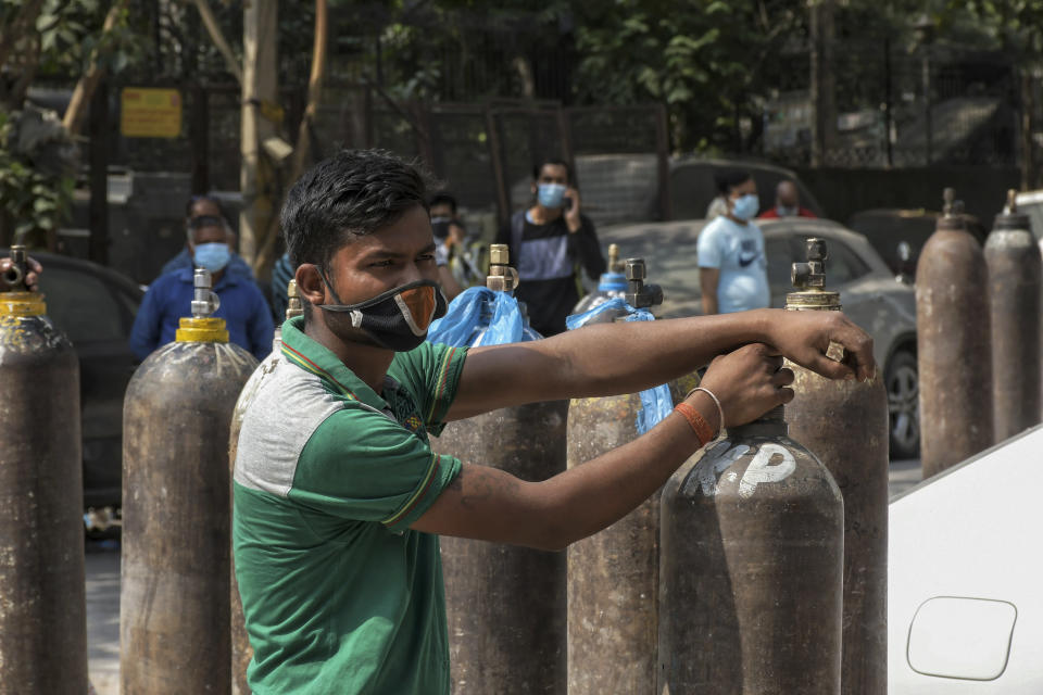 Family members of COVID-19 patients wait in queue to refill their oxygen cylinders at Mayapuri area in New Delhi, India, Monday, May 3, 2021. Indian hospitals are struggling to secure a steady supply of oxygen, and more COVID-19 patients are dying amid the shortages. (AP Photo/ Ishant Chauhan)