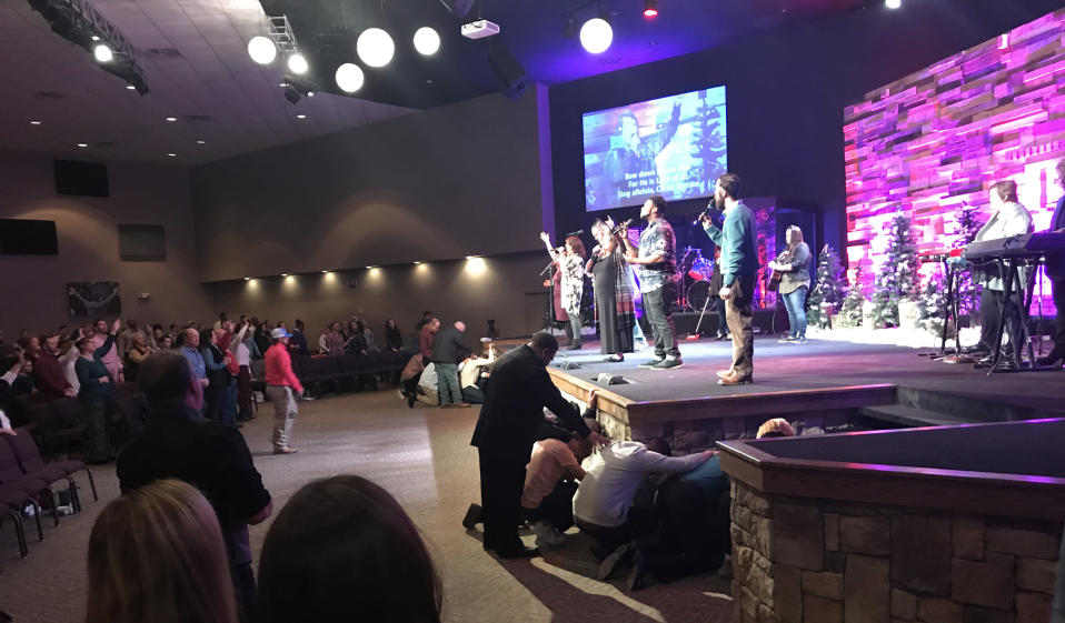 """Worshipers kneel in front of the stage at Cornerstone Church in Choccolocco, Ala., as the congregation sings, """"O come to the altar, the Father's arms are open wide."""" (Photo: Jon Ward/Yahoo News)"""