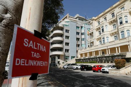 """A placard reading: """"A kingdom of delinquents"""" is seen outside Whitehall Mansions, which houses the Maltese-registered Pilatus Bank, in Ta' Xbiex, Malta March 21, 2018. REUTERS/Darrin Zammit Lupi"""