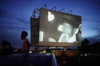 """People watch a documentary called """"Rebuilding Black Wall Street,"""" during a drive-in screening of documentaries during centennial commemorations of the Tulsa Race Massacre, Wednesday, May 26, 2021, in Tulsa, Okla. (AP Photo/John Locher)"""
