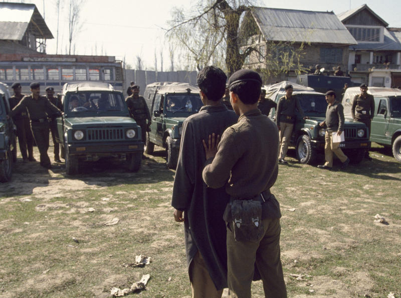 An Indian Border Security Force soldier shows a suspected militant to people in a line of parked military vehicles, Srinagar, India, on July 28, 1994. | Robert Nickelsberg—Getty Images