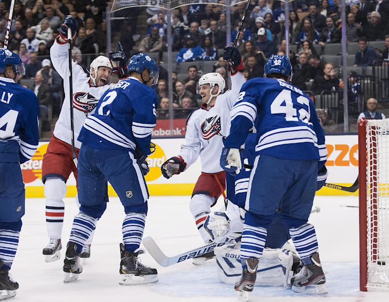 Columbus Blue Jackets' RJ Umberger, left, celebrates with teammate Blake Comeau, right, after scoring against Toronto Maple Leafs goalie James Reimer during the first period of an NHL hockey game in Toronto on Monday, Nov. 25 2013. (AP Photo/The Canadian Press, Aaron Vincent Elkaim)