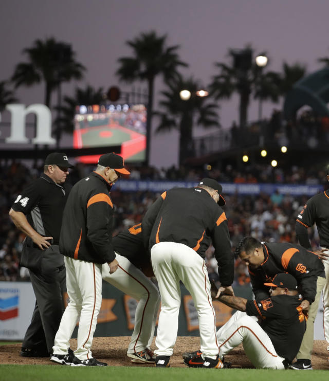 San Francisco Giants pitcher Reyes Moronta, right, is helped to his feet after falling with an injury during the sixth inning of the team's baseball game against the San Diego Padres on Saturday, Aug. 31, 2019, in San Francisco. Moronta left the game. (AP Photo/Ben Margot)