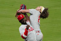 Philadelphia Phillies third baseman Alec Bohm (28) collides with left fielder Andrew McCutchen (22) as he catches a Atlanta Braves' Ozzie Albies pop fly in foul territory in eighth inning of a baseball game Saturday, April 10, 2021, in Atlanta. (AP Photo/John Bazemore)
