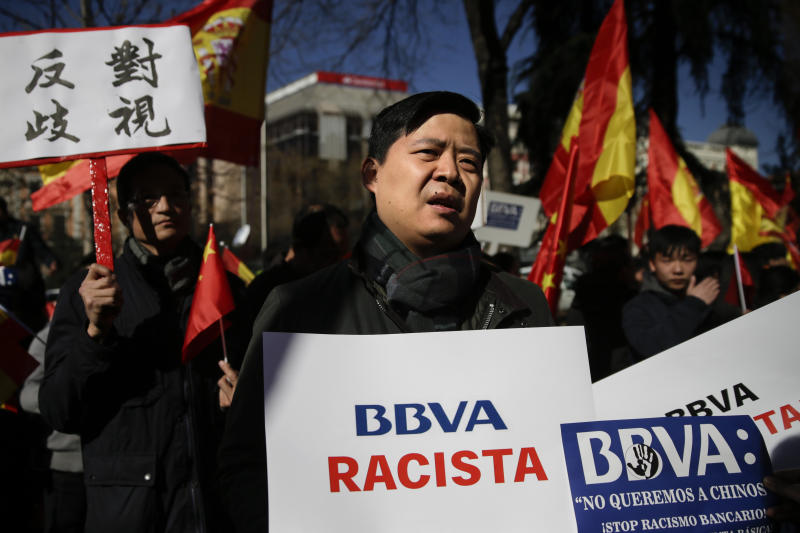 """A man protests holding a banner reading in Spanish """"BBVA racist"""" outside a BBVA bank building in Madrid, Spain, Friday, Feb. 15. 2019. Hundreds of Chinese have protested outside a Spanish bank's premises in Madrid, claiming they are being denied access to their accounts while the bank insists it is obeying money-laundering laws. (AP Photo/Andrea Comas)"""
