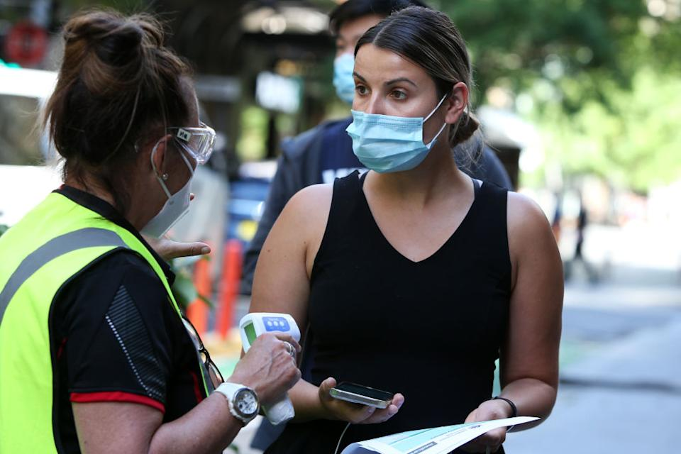 A healthcare worker assists a person as they arrive to check in at the Sonic Healthcare Covid-19 Vaccination hub in the CBD.