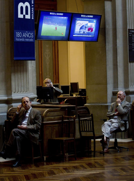 Brokers work as an image of the Euro 2012 soccer tournament appears on a screen at the Stock Exchange in Madrid Monday June 18, 2012. Spanish markets breathed a sigh of relief Monday with stocks opening higher and the country's borrowing costs dipping slightly after pro-bailout parties won the elections in Greece. Spain is a focus of fears it might be the next eurozone country to need a full bailout. The government is to announce this week how much of a euro100 billion fund it will tap to rescue banks that got burned when a real estate bubble popped. (AP Photo/Paul White)