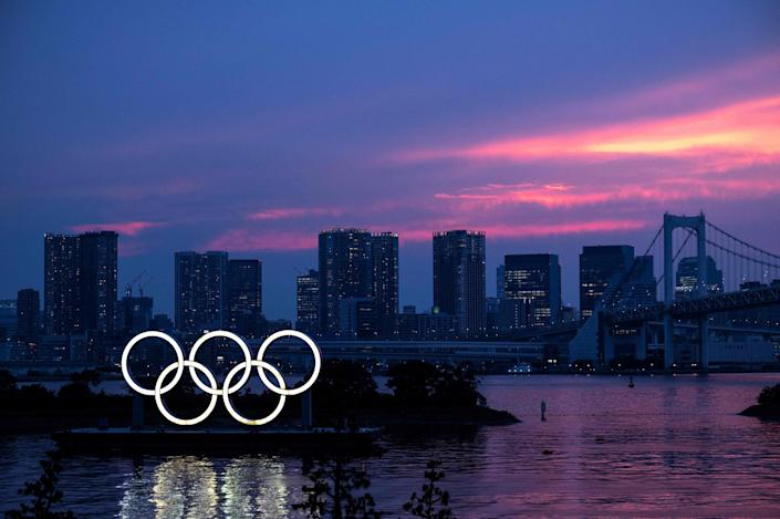 A general view shows the Olympic rings lit up at dusk, with the Rainbow bridge in the background, on the Odaiba waterfront in Tokyo (AFP via Getty Images)