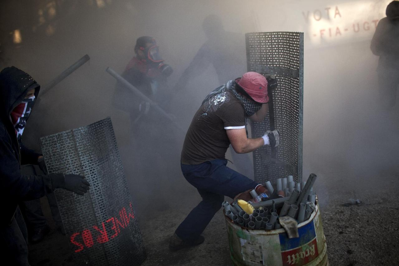 """Miners run from tear gas fired by riot police officers as they try to defend their position inside the mine """"El Soton"""" during clashes in El Entrego near Oviedo, Spain, Friday, June 15, 2012. Strikes, road blockades, and mine sit-ins continue as 8,000 mineworkers at over 40 coal mines in northern Spain continue their protests against government action to cut coal subsidies. (AP Photo/Emilio Morenatti)"""