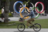 A woman rides a bicycle near the Olympic Rings Wednesday, June 2, 2021, in Tokyo. (AP Photo/Eugene Hoshiko)