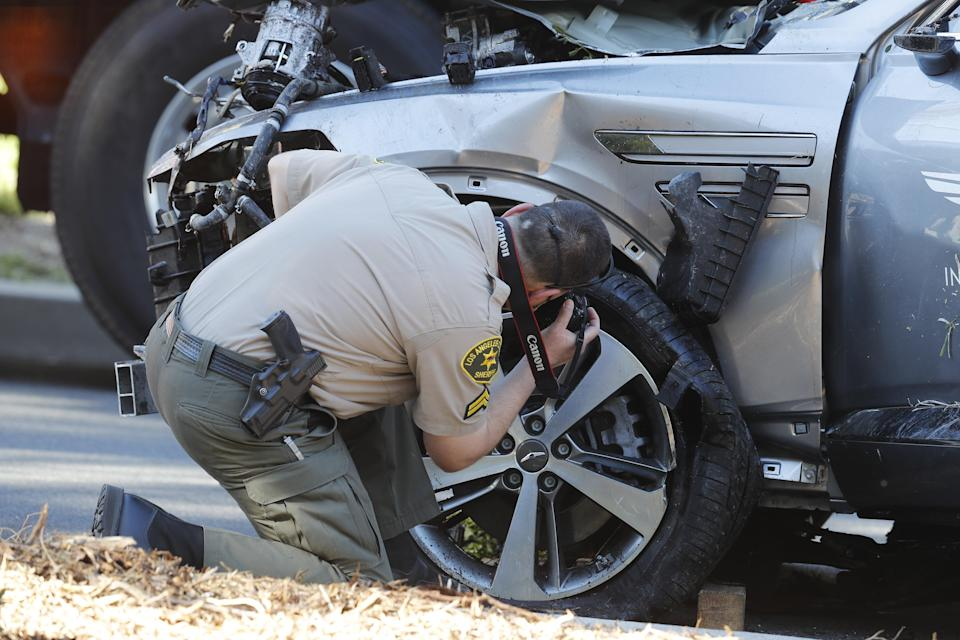 <p>A sheriff's deputy examines the SUV crashed by Tiger Woods last week</p> (EPA)