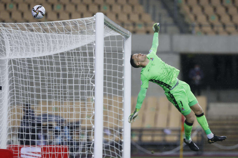 Real Sociedad's goalkeeper Alex Remiro jumps to save on a shot on goal by Athletic Bilbao's Inigo Martinez during the final of the 2020 Copa del Rey, or King's Cup, soccer match between Athletic Bilbao and Real Sociedad at Estadio de La Cartuja in Sevilla, Spain, Saturday April 3, 2021. The game is the rescheduled final of the 2019-2020 competition which was originally postponed due to the coronavirus pandemic. (AP Photo/Angel Fernandez)