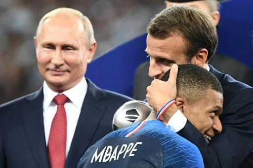 French President Emmanuel Macron congratulates striker Kylian Mbappe, whose parents hail from Cameroon and Algeria, as Russian President Vladimir Putin looks on