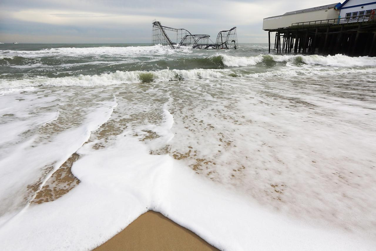 SEASIDE HEIGHTS, NJ - NOVEMBER 16: Waves break in front of a destroyed roller coaster on November 16, 2012 in Seaside Heights, New Jersey. Two amusement piers and a number of roller coasters in the seaside town were destroyed by Superstorm Sandy.   (Photo by Mario Tama/Getty Images)