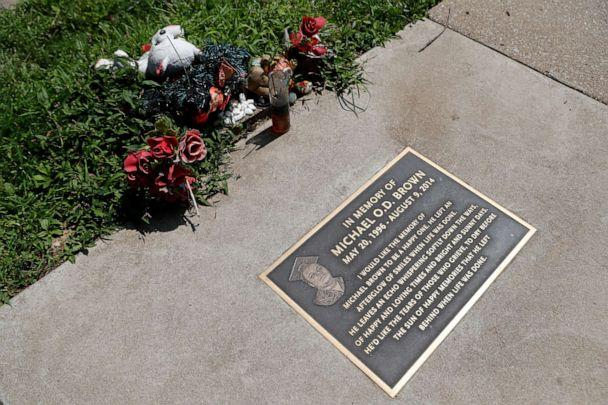 PHOTO: In this July 25, 2019, photo, flowers and other items lay near a memorial plaque in the sidewalk near the spot where Michael Brown was shot and killed by a police officer five years ago in Ferguson, Mo. (Jeff Roberson/AP)