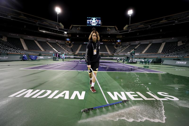 Courtmaster Jeffrey Brooker sprays and cleans the centre court at the Indian Wells Tennis Garden.