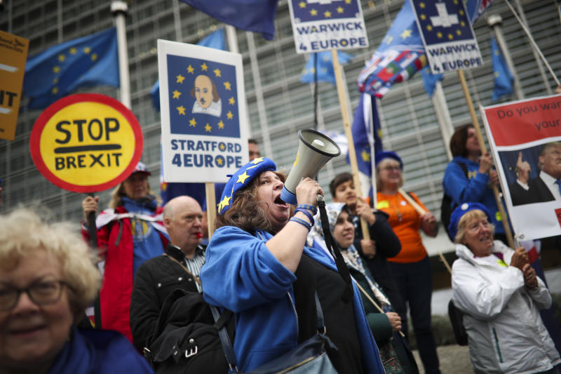 People shout slogans during an anti-Brexit protest outside the European Commission headquarters in Brussels, Wednesday, Oct. 9, 2019. A small group of anti-Brexit campaigners has staged a protest at the European Commission's headquarters in Brussels asking for a rejection of British Prime minister Boris Johnson's proposals for his country's planned exit from the bloc. (AP Photo/Francisco Seco)