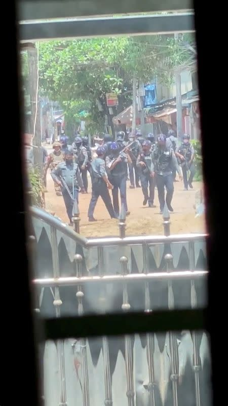 Security officers walk down the street during crackdown in Bago