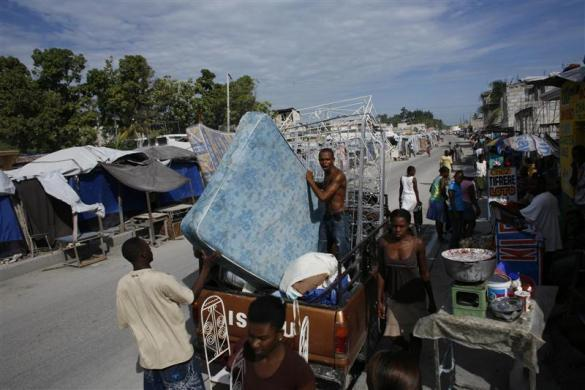 Residents load their belongings into a truck to move to another town, in a street known as Route des Rails in Port-au-Prince, July 22, 2010.
