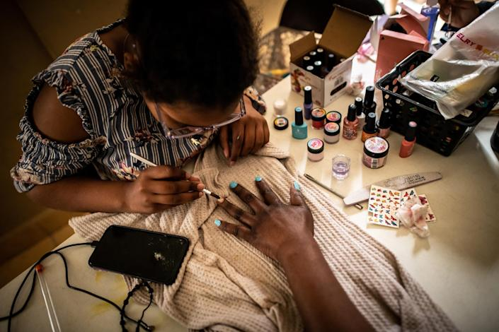 "Migrants give each other gel manicures. Manicuring is one of the most accessible jobs migrant women can attain to earn an income in Ciudad Juárez. The shelter funds some women to get professional training, and then they share what they've learned by training other women at the shelter.<span class=""copyright"">Meridith Kohut for TIME</span>"