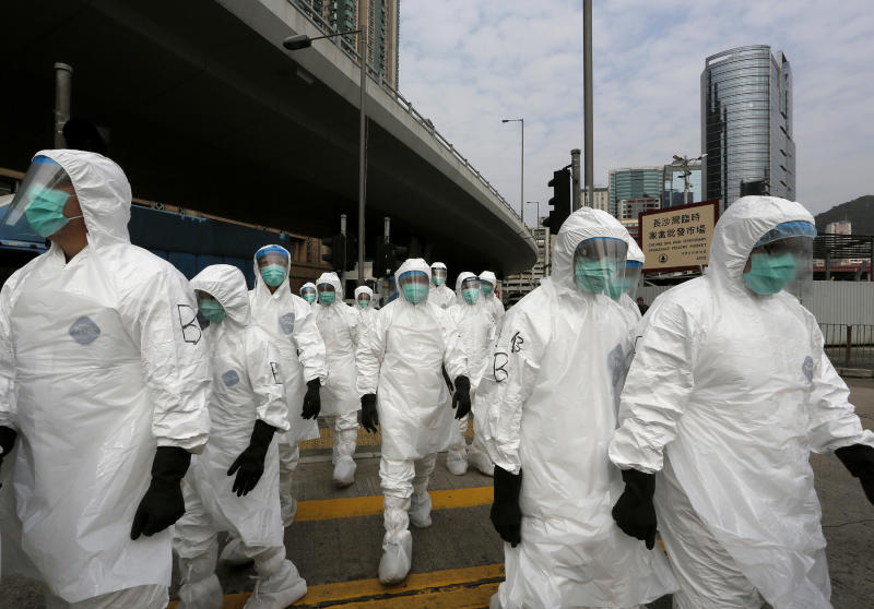 Health workers in full protective gear walk at a wholesale poultry market before culling the poultry in Hong Kong, Tuesday, Jan. 28, 2014. Hong Kong authorities began culling 20,000 birds at the wholesale market after poultry from southern mainland China tested positive for the H7N9 virus, the first time it had been found in imported poultry in Hong Kong. (AP Photo/Vincent Yu)