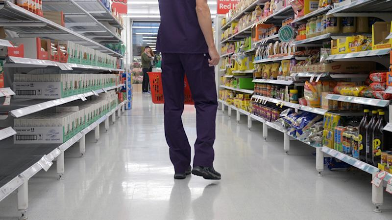 Coles has re-introduced purchase limits as of June 26. A shopper carries a basket inside one of the stores.
