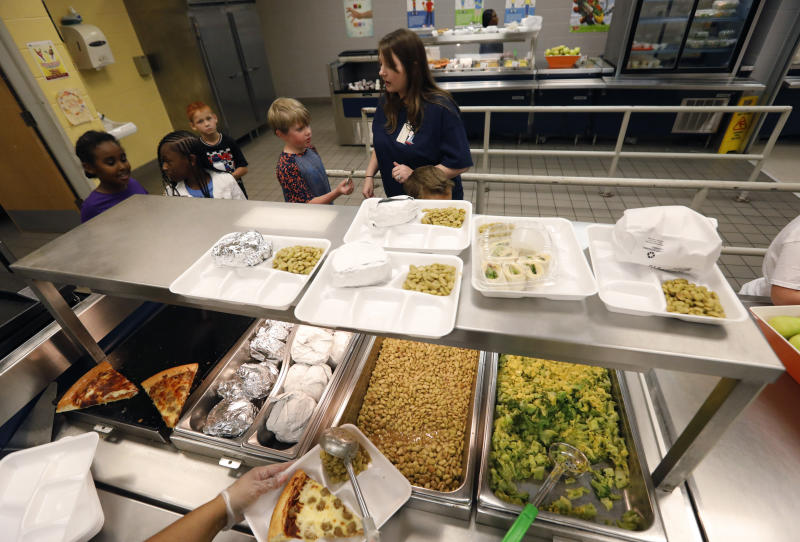 A teacher lines up the students for school-prepared lunches at Madison Crossing Elementary School in Canton, Miss., Friday, Aug. 9, 2019. Scott Clements, director of child nutrition at the Mississippi education department, said they've ordered two truckloads of trade mitigation pulled pork and four loads of kidney beans for use in their cafeterias. The products are coming from the U.S. Department of Agriculture, which is giving away the foods it's buying to help farmers hurt by trade negotiations. (AP Photo/Rogelio V. Solis)