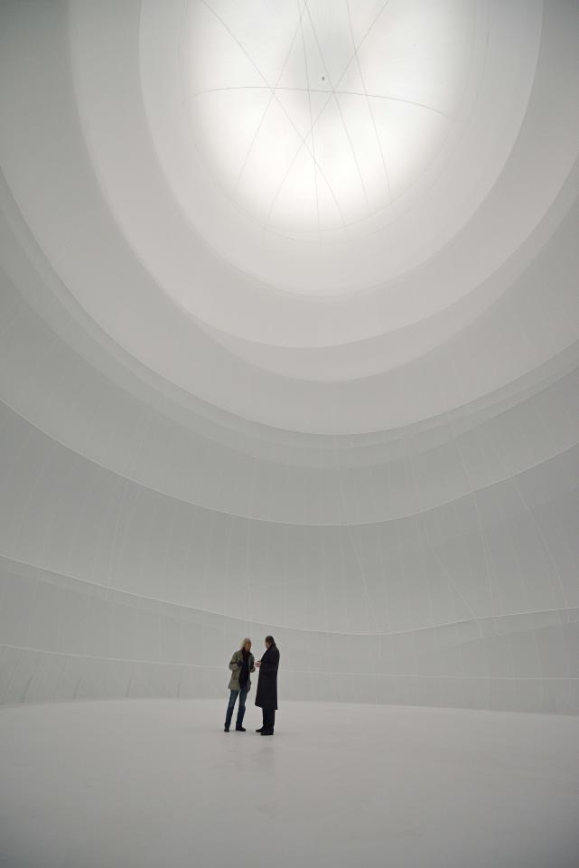 In this picture taken March 13, 2013 International artist Christo, left, stands with a visitor inside his 'Big Air Package' artwork at the Gasometer in Oberhausen, Germany, two days before the official opening of the exhibition on March 15, 2013. Christo's latest monumental sculpture in the interior of the industrial monument reaches a height of more than 90 metres, a diameter of 50 metres and a volume of 177,000 cubic metres. The world's largest self-supporting sculpture will be on show to the public from March 16 to Dec. 30, 2013. (AP Photo/Martin Meissner)